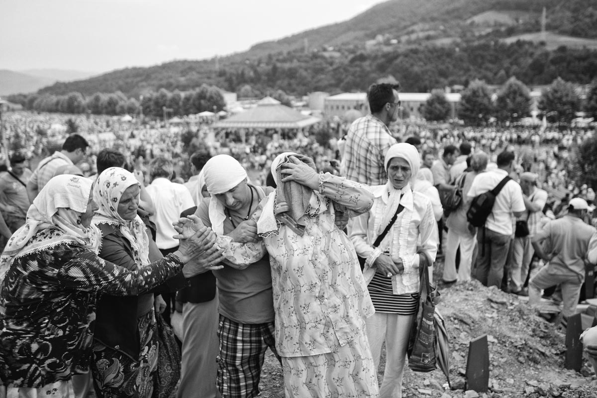 a family mourns as their relative is being enterred, potocari graveyard, bosnia, 2011.