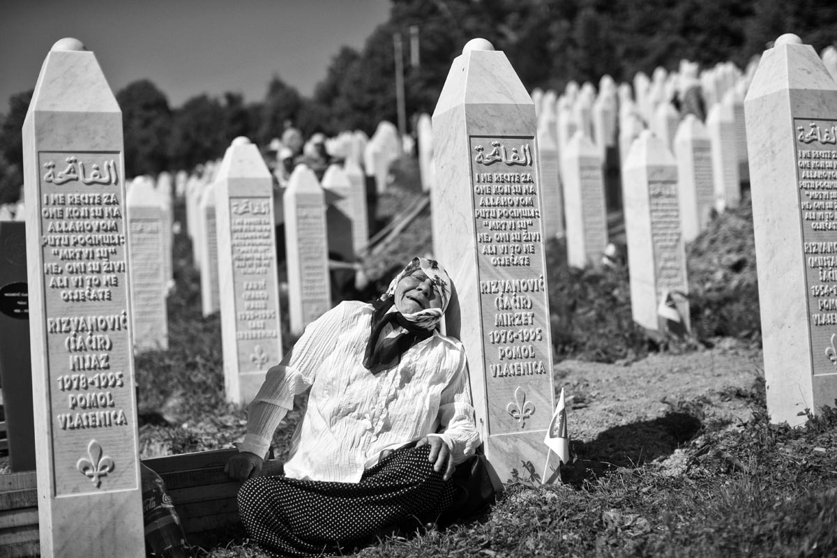 a woman cries next to tombstones of her two sons, victims of the srebrenica genocide, potocari cemetery, bosnia, 2015.