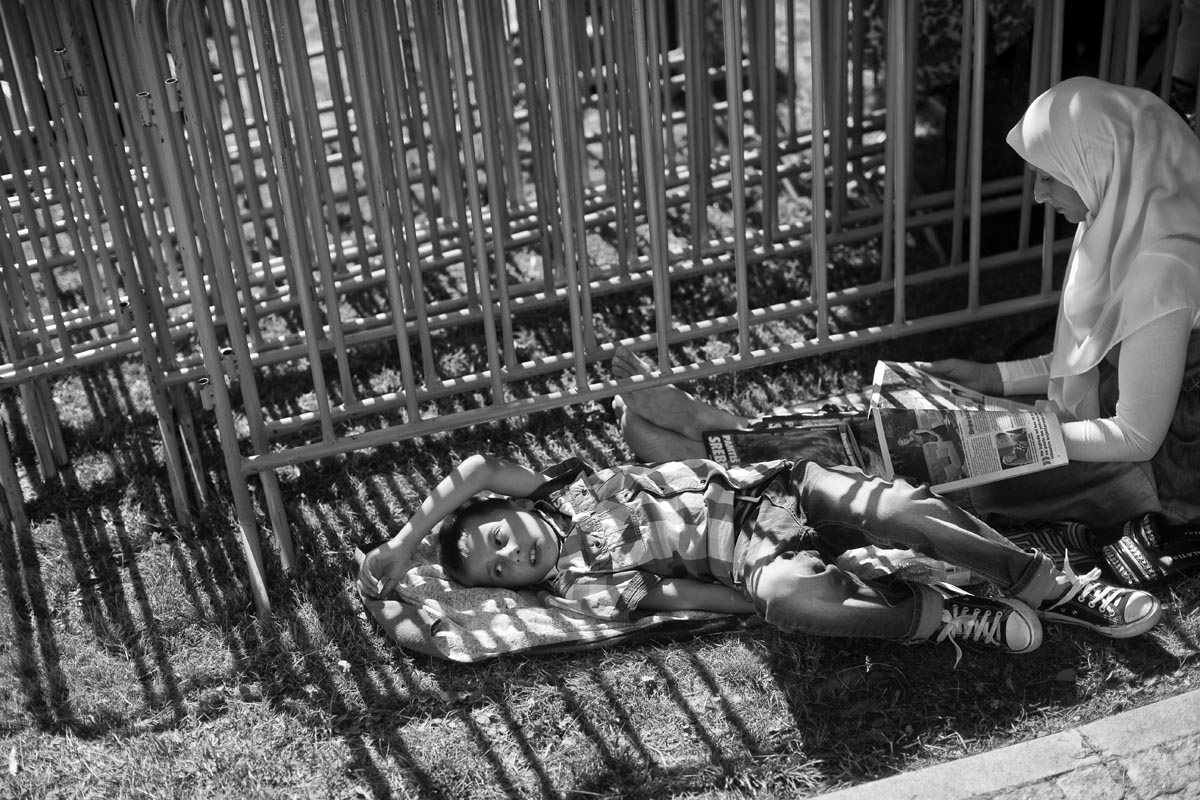 a child and his mother rest under a shade, potocari cemetery, bosnia, 2015.