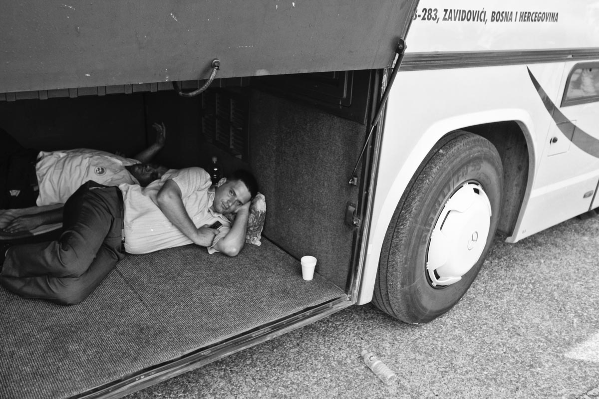 two men rest inside the baggage space of a bus, potocari memorial complex, bosnia, 2010.