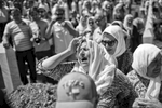 a woman cries as she buries the remains of her son, potocari cemetery, bosnia, 2015.
