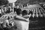 two men brace each other as they grieve, potocari cemetery, bosnia, 2011.