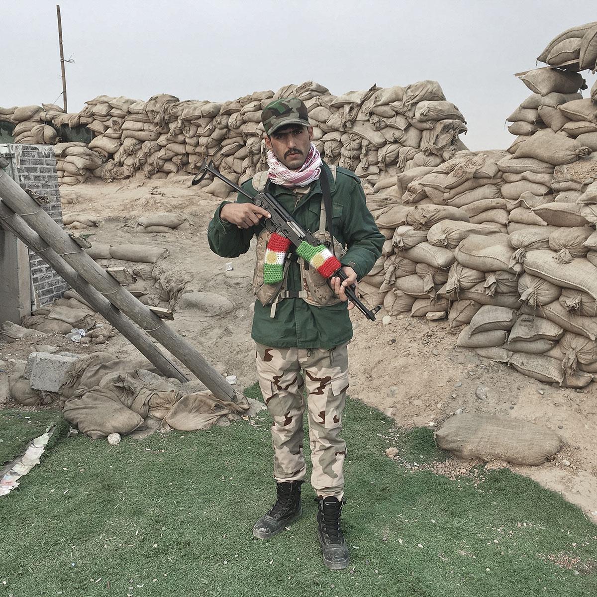 Hiwa Omar, 25, a Kurdish Peshmerga from Irbil, Iraq, guards a checkpoint in Gwer, southeast of Mosul, Iraq, Oct. 24, 2016.