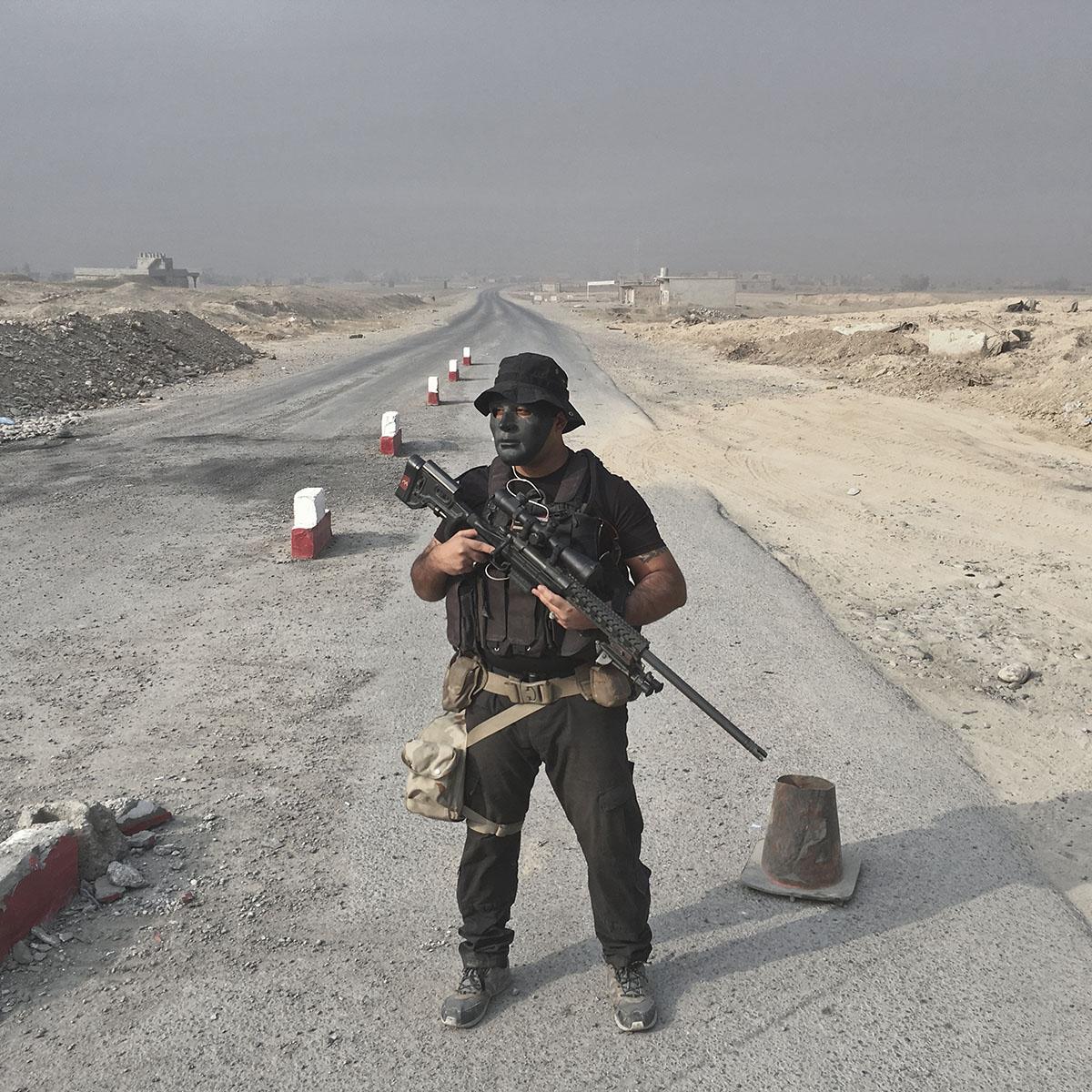 Riyad Jaffar, 27, from Baghdad, Iraq, an army sniper, mans a checkpoint on the outskirts of Qayara, south of Mosul, Iraq, Oct. 26, 2016.