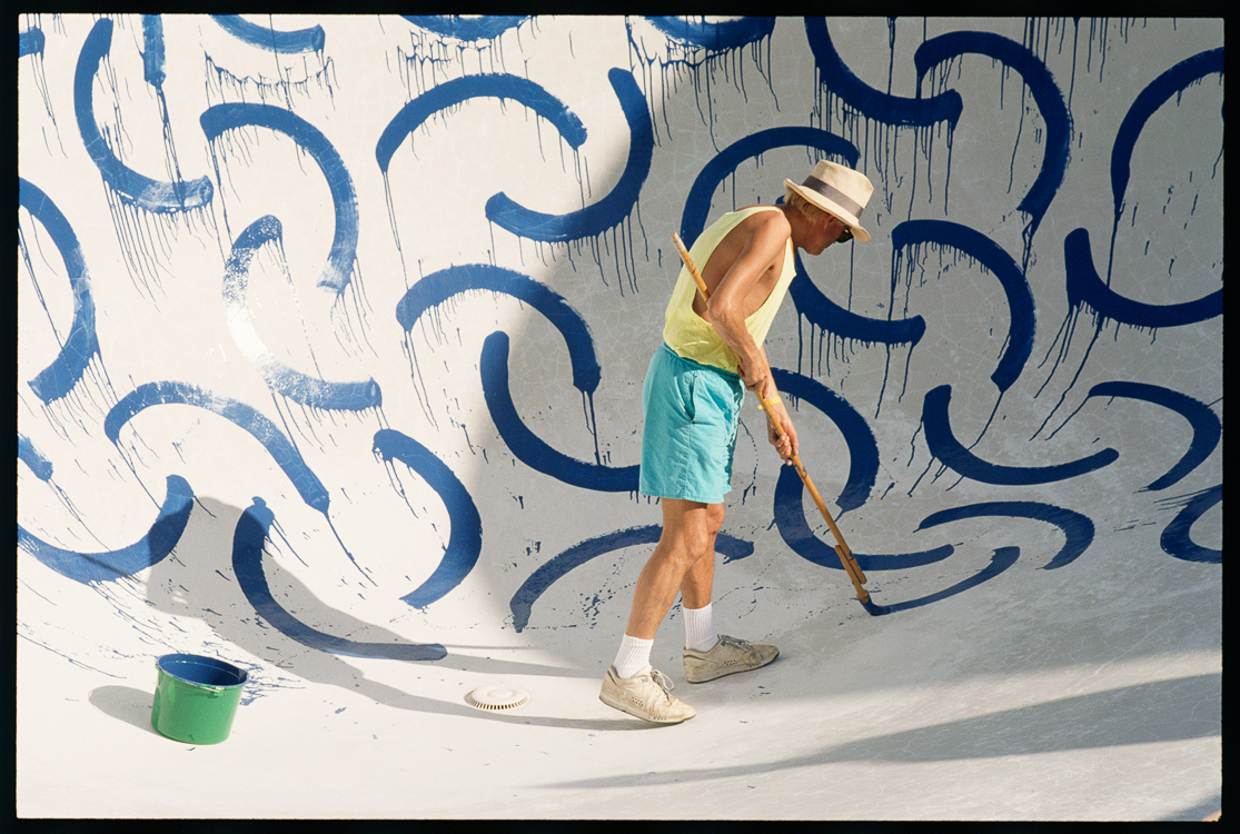 David Hockney painting a swimming pool in Los Angeles as a generous auction gift for an AIDs benifit. A master draftsman, each semi-circle, drawn by hand, with a brush fixed to the end of a long pole, is spaced and executed perfectly.