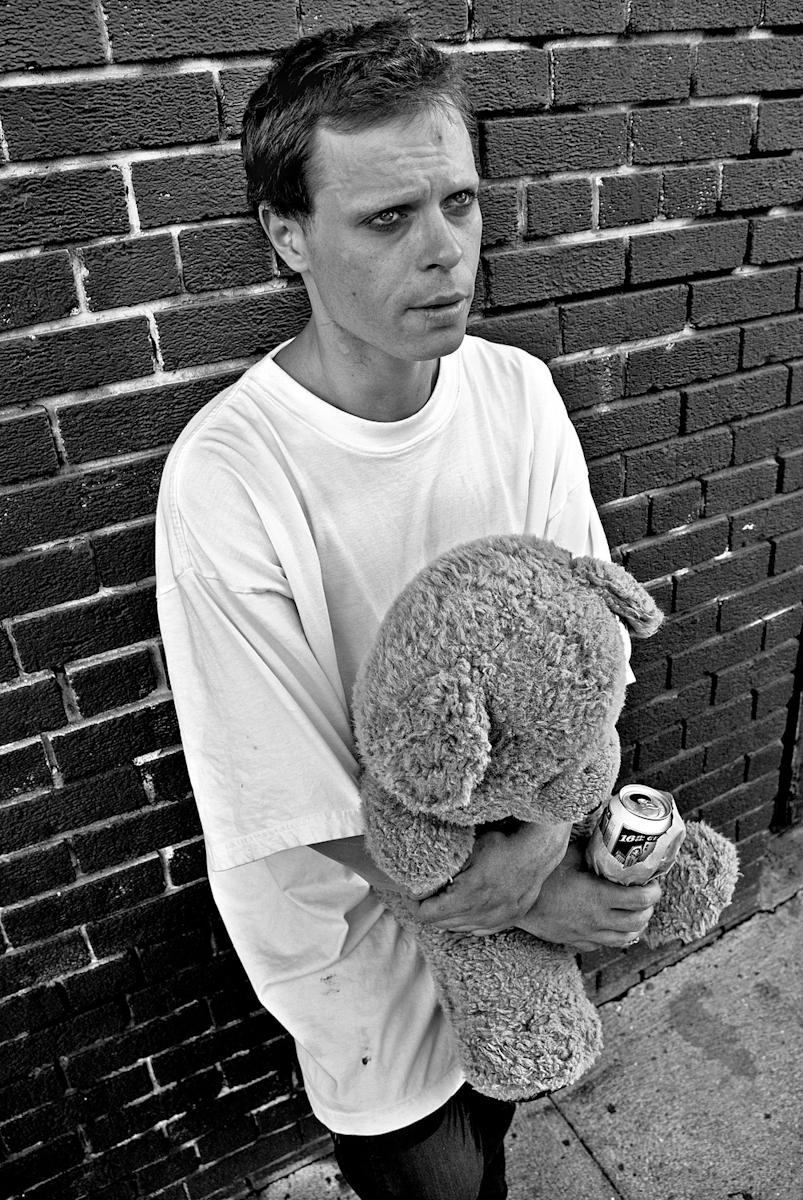 YOUNG MAN WITH TEDDY BEAR, SAN FRANCISCO, OCTOBER 2007he's been working the intersection like a pin ball, or a yo-yo on a string. corner to corner; side to side. propelled or drawn, he rushes here and there, then waits.i catch him in an alley with a friend and his bear. the friend is hunched behind a car and hovers away as i approach. the bear stays close.name's wayland; from san mateo. been more than a year since i met him first.he tells me of the places he's been and the places he likes. says he likes colorado best because people get along good there. he went there with his parents when he was about fifteen.they took his picture with a baseball cap and his baseball glove raised to make a catch. he shows me how. says he was really close to his parents and he misses them.they're dead now. his mom died in '97 from stomach cancer and his dad might as well have. his dad started shooting meth, got aids from a transvestite downtown and died soon after.the transvestite was a friend of wayland's and he's pretty sure she's how his dad got infected. he's not totally sure though.but he's sure it wasn't him.{quote}i had myself checked. it wasn't me. i'm just glad i didn't give it to him.{quote}