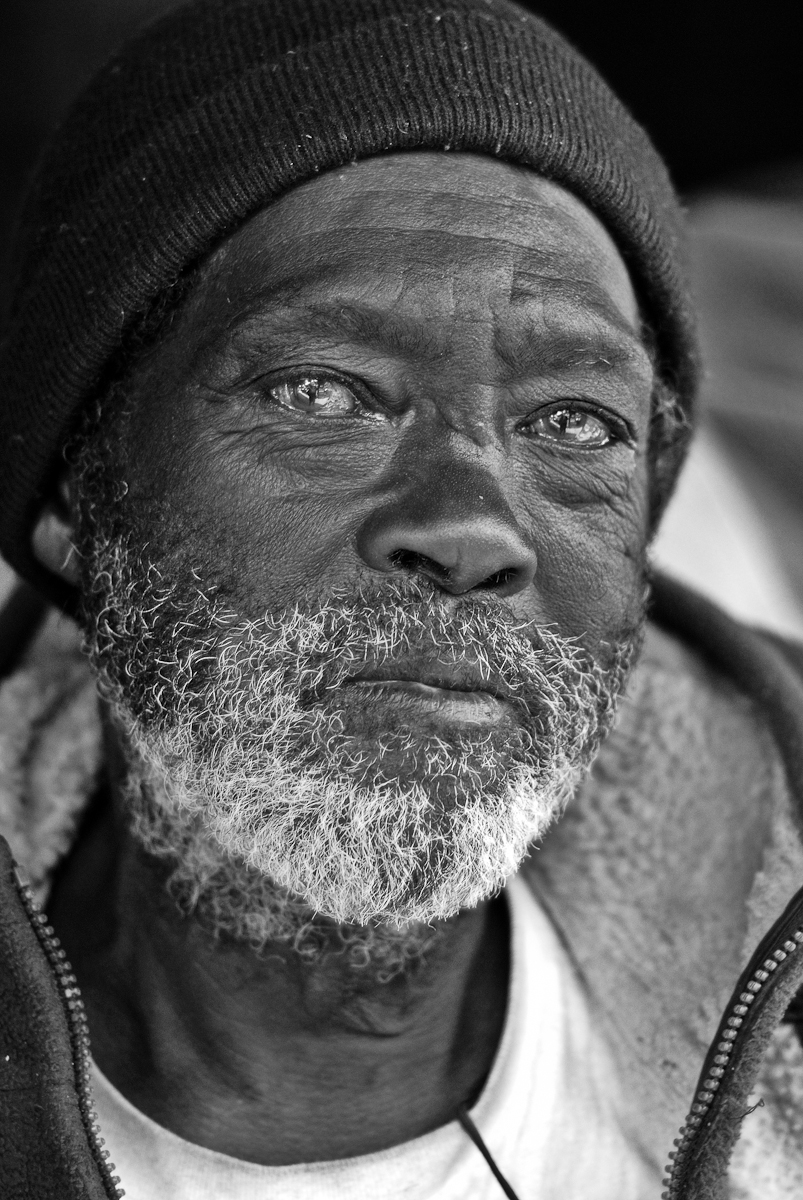 MAN HOMELESS AND TIRED, SAN FRANCISCO, APRIL 2006he stands in a doorway in the mission shaded from the sun. been homeless for a while now. name's walter; from texas. he was living along katrina's path when it struck. displaced, he returned to san francisco soon after. says he always liked it here.says he has two daughters with three doctorates between them; one who teaches at columbia; the other at texas southern.he was one of the original twelve black panther founding members, he says. i tell him my mother worked with eldridge cleaver at ramparts magazine back in the day. but he says he never liked cleaver: {quote}he wasn't good to his woman.{quote}says men are crooks. all of them… {quote}you and me, we're men; but we know.{quote} he smiles with a quick wink.he says we need to return to where we came from; women need to run the show. {quote}just think{quote}, he continues, {quote}who raised you? who took care of you? who managed the household? your mother, that's who. and your grandmother. i never disrespected a woman in my life; and i never will.{quote}{quote}we need a woman president{quote} he insists; {quote}to fix things. no more men. we only fuck it up.{quote}{quote}we need hillary {quote} he says. {quote}you think i'm foolin'; i'm serious!{quote}{quote}me{quote} he finishes, {quote}i'm just waiting for god to take me away. i don't like what i see in this place.{quote}(4/23/06)