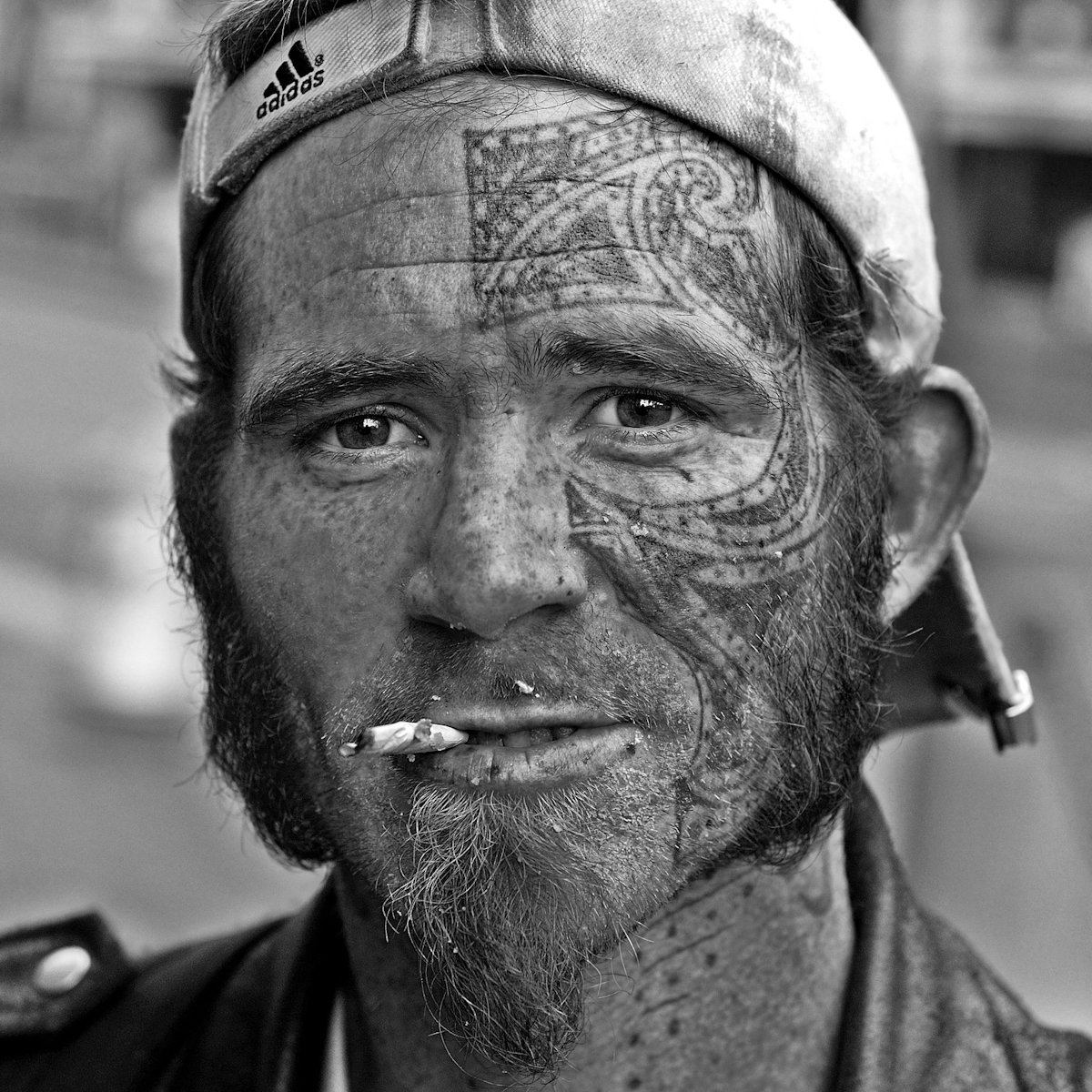 DRIFTER LEIF WITH FACE TATTOO IN TENDERLOIN, SAN FRANCISCO, MAY 2006homeless man from texas. he's off to los angeles as soon as he can scrape together the cash. got his tattoo done years ago at a place called the mystic mark.when i first saw him, he was checking through some leaves by the curb. he has debris on his face.his name is leif; pronounced {quote}life.{quote}(5/3/06)