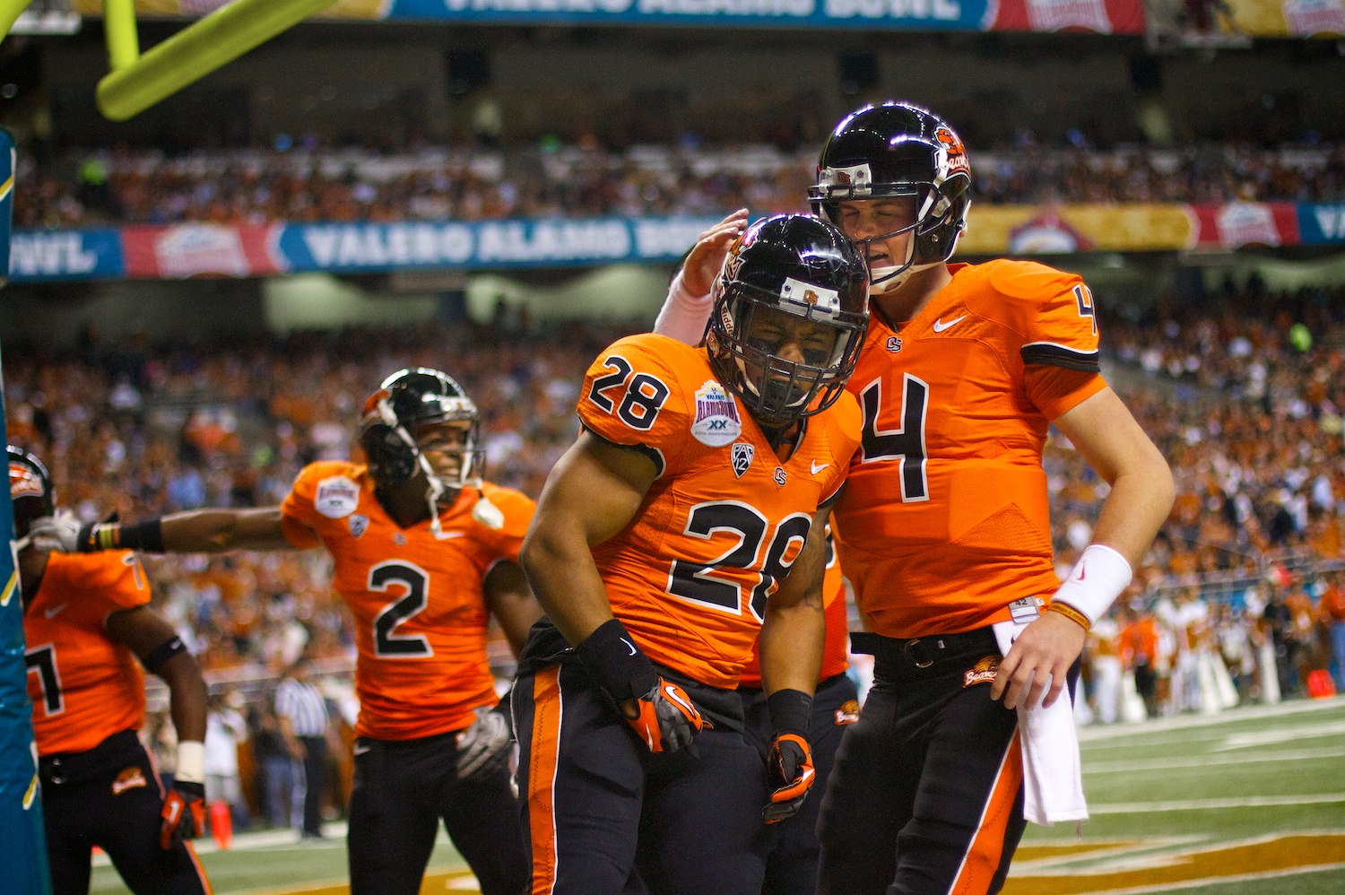 Sean Mannion (4) and Terron Ward (28) celebrate after scoring a touchdown during the 2012 Valero Alamo Bowl in San Antonio, Texas.