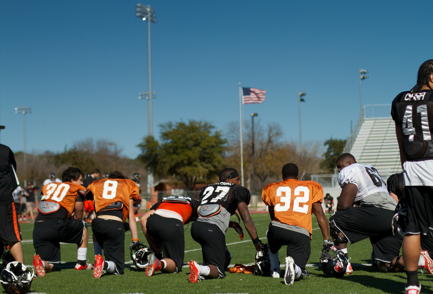 Players take a break on the sidelines during a practice leading up to the Alamo Bowl in San Antonio, Texas.