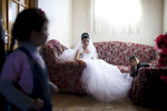 A 17-year-old Georgian-Azeri bride in the Kakheti Region waits for the groom to arrive on their wedding day. She and her 22-year-old husband-to-be met one month earlier, the day their engagement was announced.