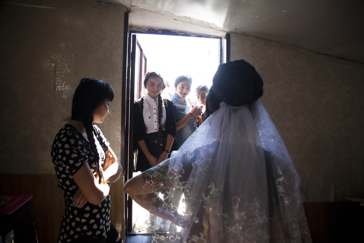 A bride's classmates visit her before the wedding to see her dress.