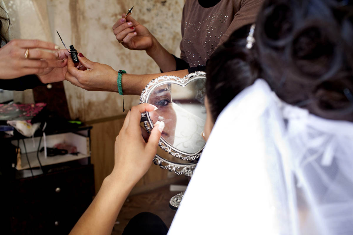 Georgian-Azeri Bride putting on make-up for her wedding ceremony at a local village Salon.