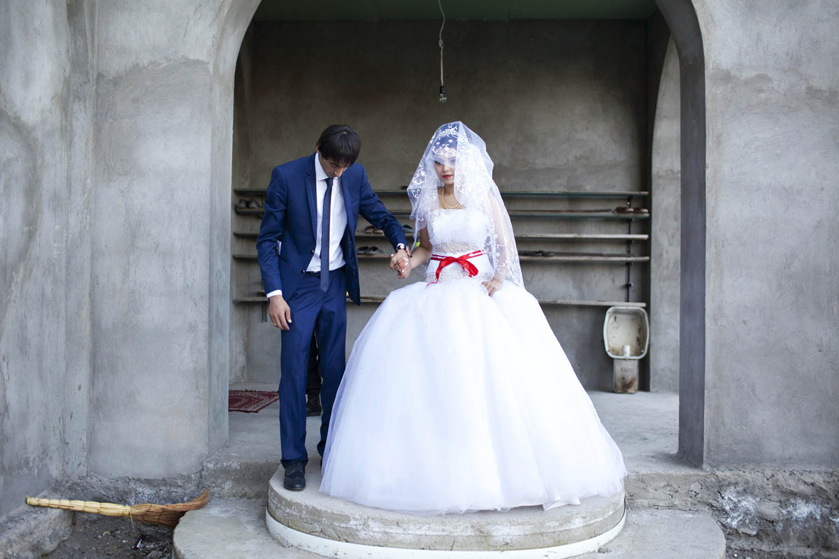 A Georgian-Azeri couple, who are Muslim, pose in front of a mosque on their wedding day. They met one month earlier, the day their engagement was announced. She is 17 and he is 22.