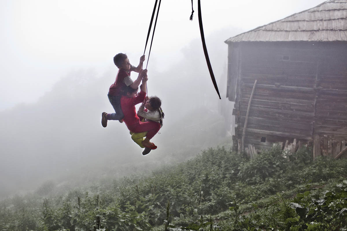 Friends swinging on a hand made swing on a foggy day. Adjara region is most common for early marriages, where young girls marry before school, following the footsteps of family tradition.