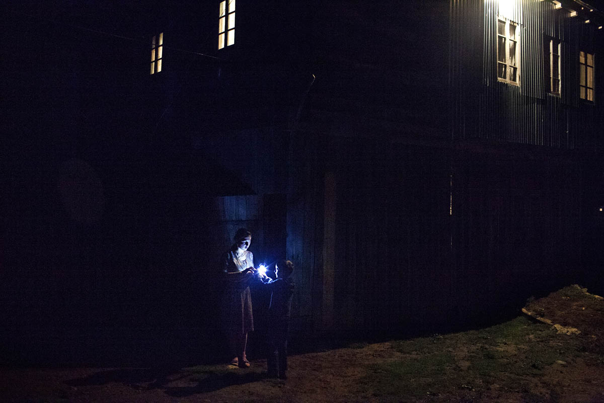 Night in Mountanious Adjara region. Newly engaged girl, giving a flashlight to her neighbor. kid.