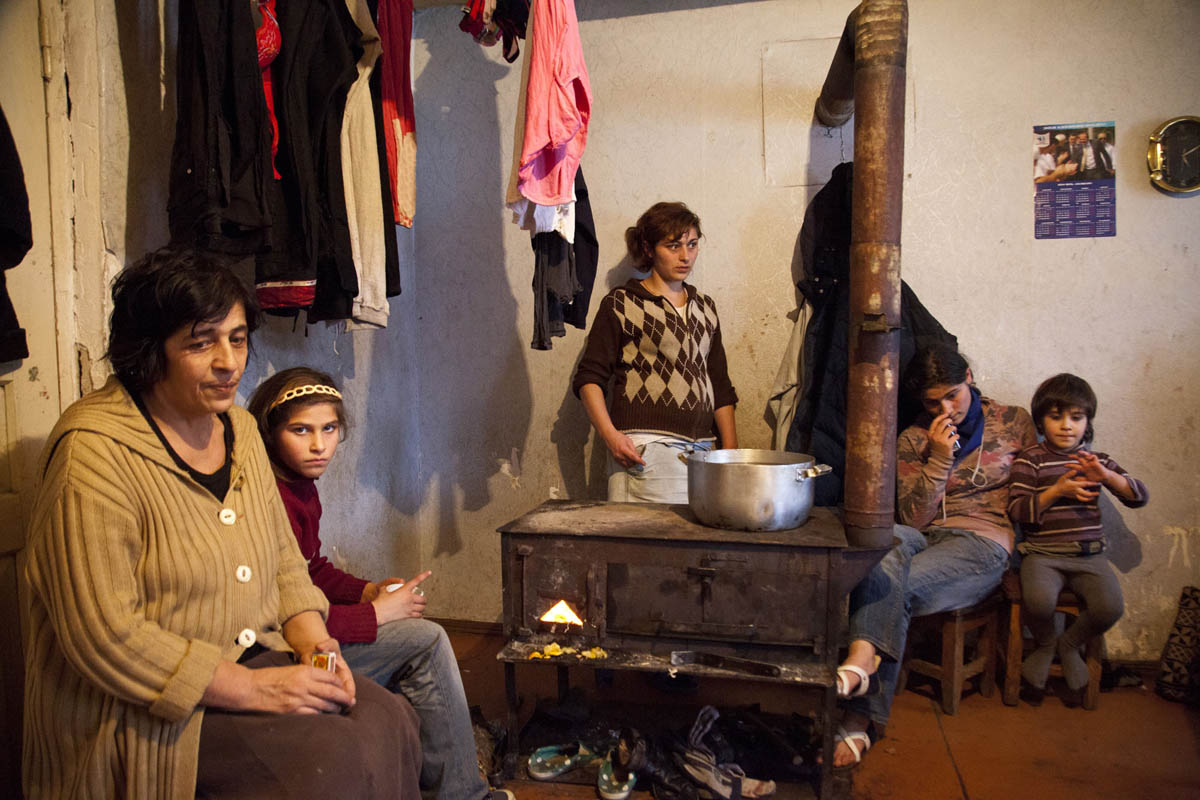 Georgia, Chiatura City. Zaza's, A miner's family sits together in their home. Zaza has 15 kids with his wife.