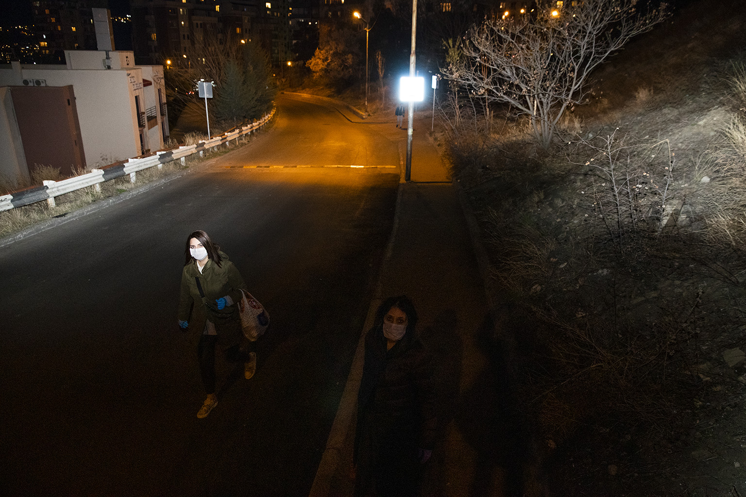 I drove outside at night to photograph during the quarantine. It was 10 p.m. but felt like 5 a.m. The streets were empty and people with face masks appeared and disappeared in empty streets.