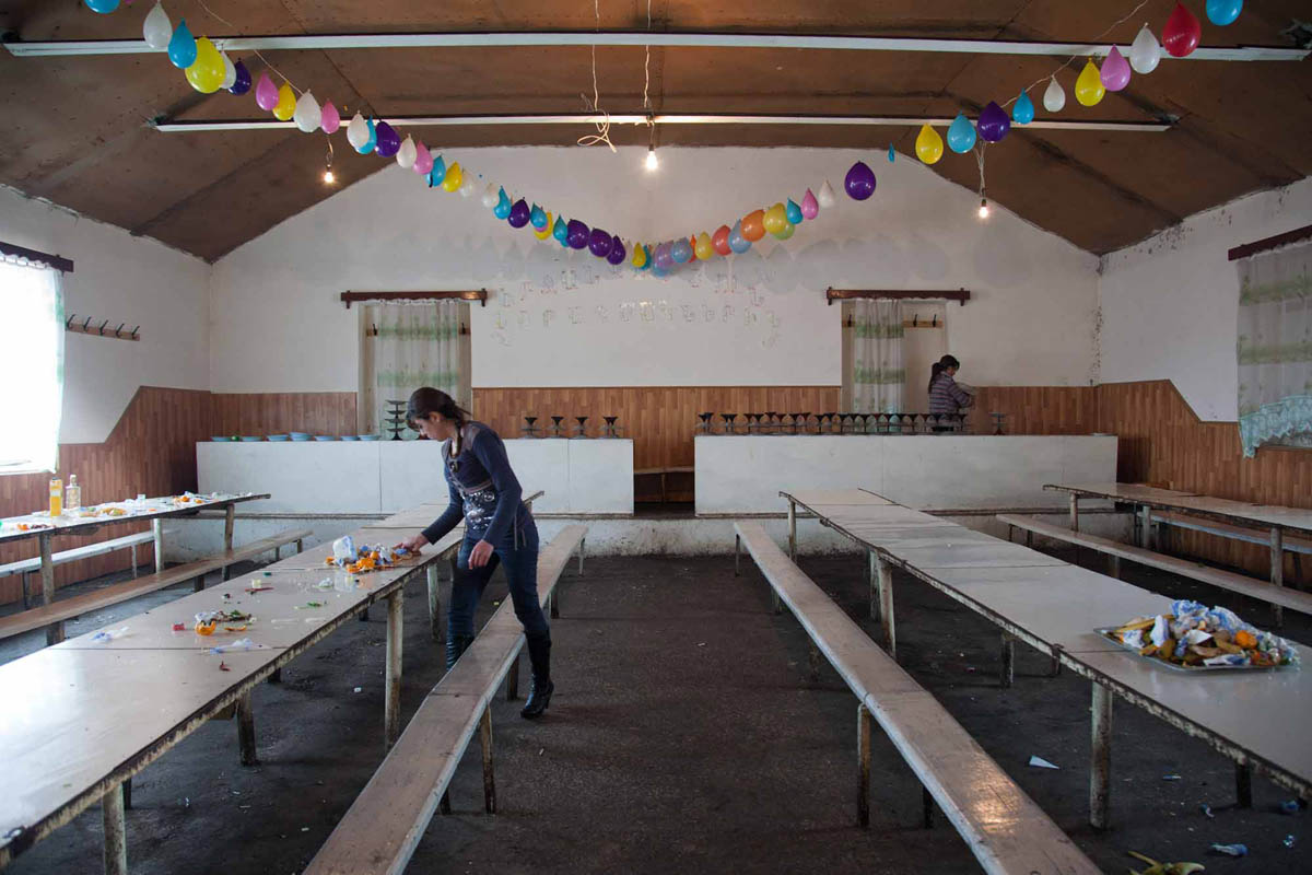 Georgia, 2012. Samtskhe – ­Javakheti region, Aragva village. Girls clean up the tables after thousands of people attended celebration of a man's survival after heart attack.