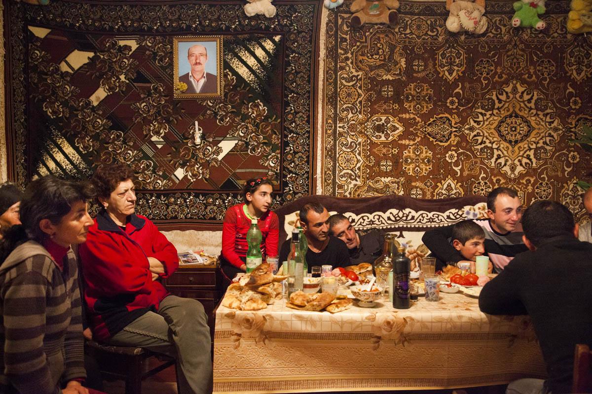 GEORGIA, 2012. Samtskhe–Javakheti Region, Poka village. An Armenian family and relatives watch TV after having hosted a feast for the film crew.