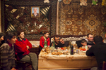 GEORGIA, 2012. Samtskhe–Javakheti Region, Poka village. An Armenian family and relatives watch TV after having hosted a feast for the film crew.
