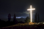GEORGIA. 2017. A brightly lit cross, erected after the 2008 Russo-Georgian War, stands on the road leading to the village of Dvani. During the conflict, up to 50 houses were burned down and bombed.