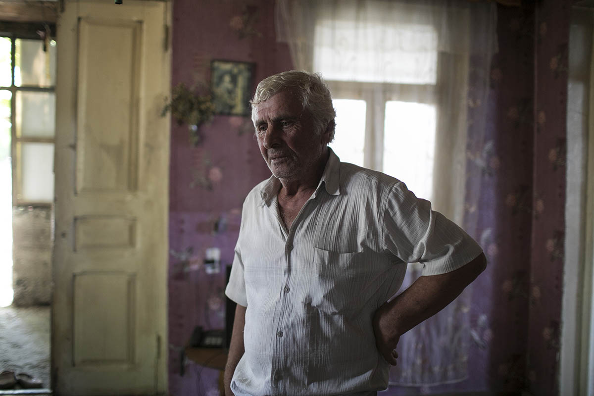 GEORGIA. 2017. Otari stands in his home in Khurvaleti village, near the southern border of South Ossetia.