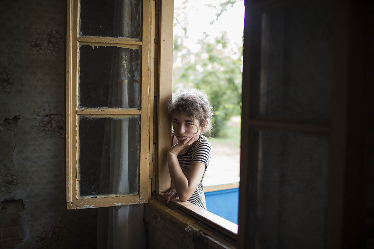 GEORGIA. 2017. Nini, a resident of the village of Khurcha, leans on a windowsill near the southeastern border of Abkhazia.