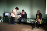 GEORGIA.  2010. Inside a Cottage, wife checks her husbands blood pressure. Tserovani. A New  village built by the Georgian government to house Georgians who were forced to flee South Ossetia when the Russians invaded.