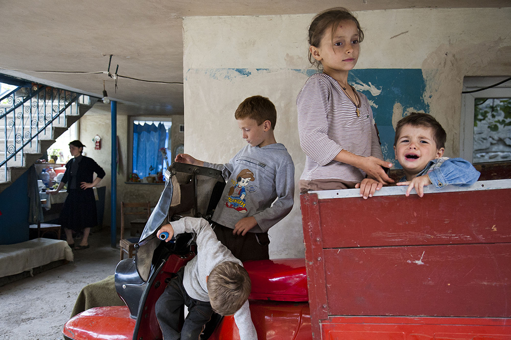2011. Georgia, Nikozi. A village near Tskhinvali, South Ossetia. A mother with her four children escaped the russian troops that invaded their village. After South Ossetian war in 2008 their house was bombed, they now live in their grandparents house, which survived the bombing.