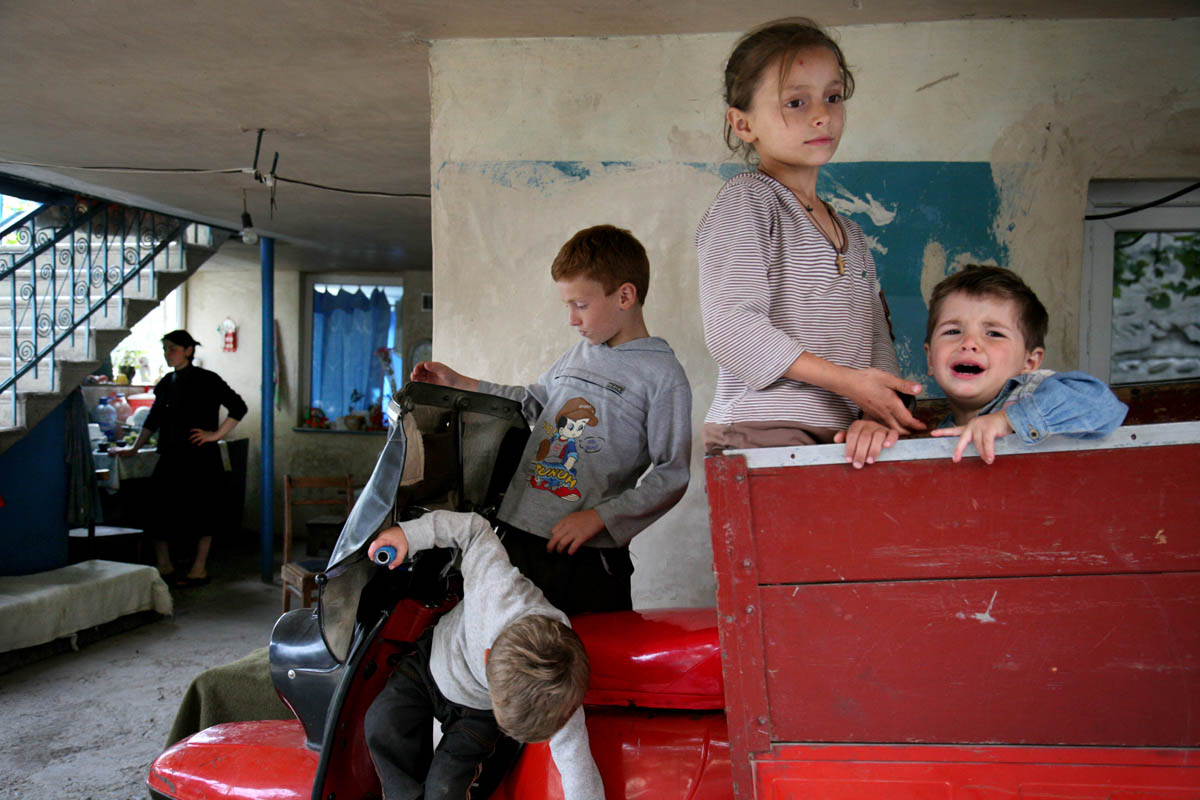 Georgia. 2010. Nikozi. A Settlement near Tskhinvali, South Ossetia. A mother with her four children now back in Nikozi after they escaped the russian troops that came in their village. After South Ossetian war in 2008 their house was bombed, they now live in their grandparents house, which survived the bombing.