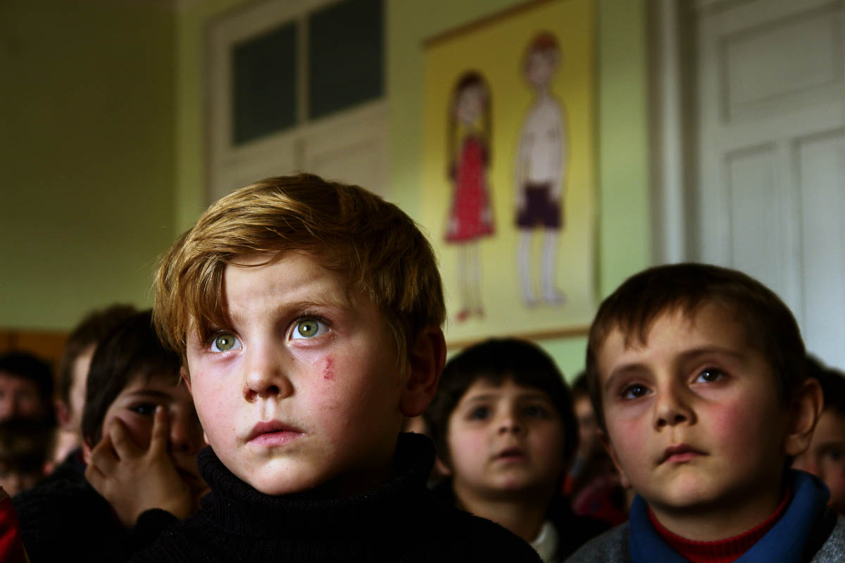 GEORGIA. Pankisi Gorge, a Chechen refugee settlement. January. 2008. Kindergarten. A boy with green eyes, Omaar, 7 years old. Omaar's family was bombed during the Chechen war while he was just a baby. He was left with his grandmother, who survived the bombing.