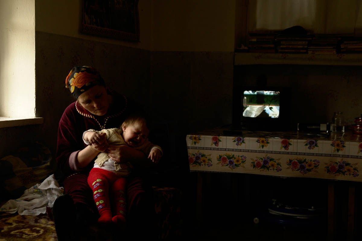 GEORGIA. Pankisi Gorge, a Chechen Refugee settlement. March. 2008. Chechen woman, Iase, with her daughter. During the war in Chechnya one of the bombs hit Iase's house in Grozny, the capital. She lost her home. Left in the streets, she followed the rest of the Chechens escaping to Georgia. Crossing the border she ended up in the Pankisi Gorge where she settled. She is still hoping to return home one day.