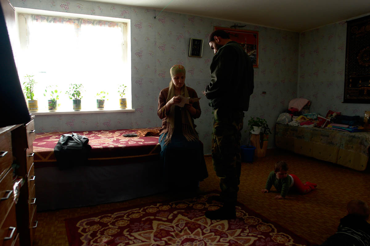 GEORGIA. Pankisi Gorge, a Chechen refugee settlement. A chechen family, husband and wife going through a family album.