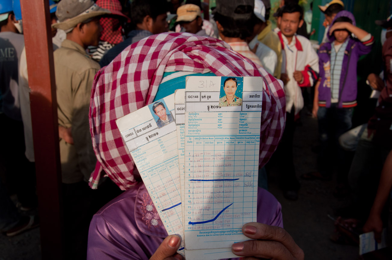 Workers handing in their time cards to get paid. Construction workers at are mostly from the countryside and earn anywhere between five to ten dollars per day depending on their skills. December 2011