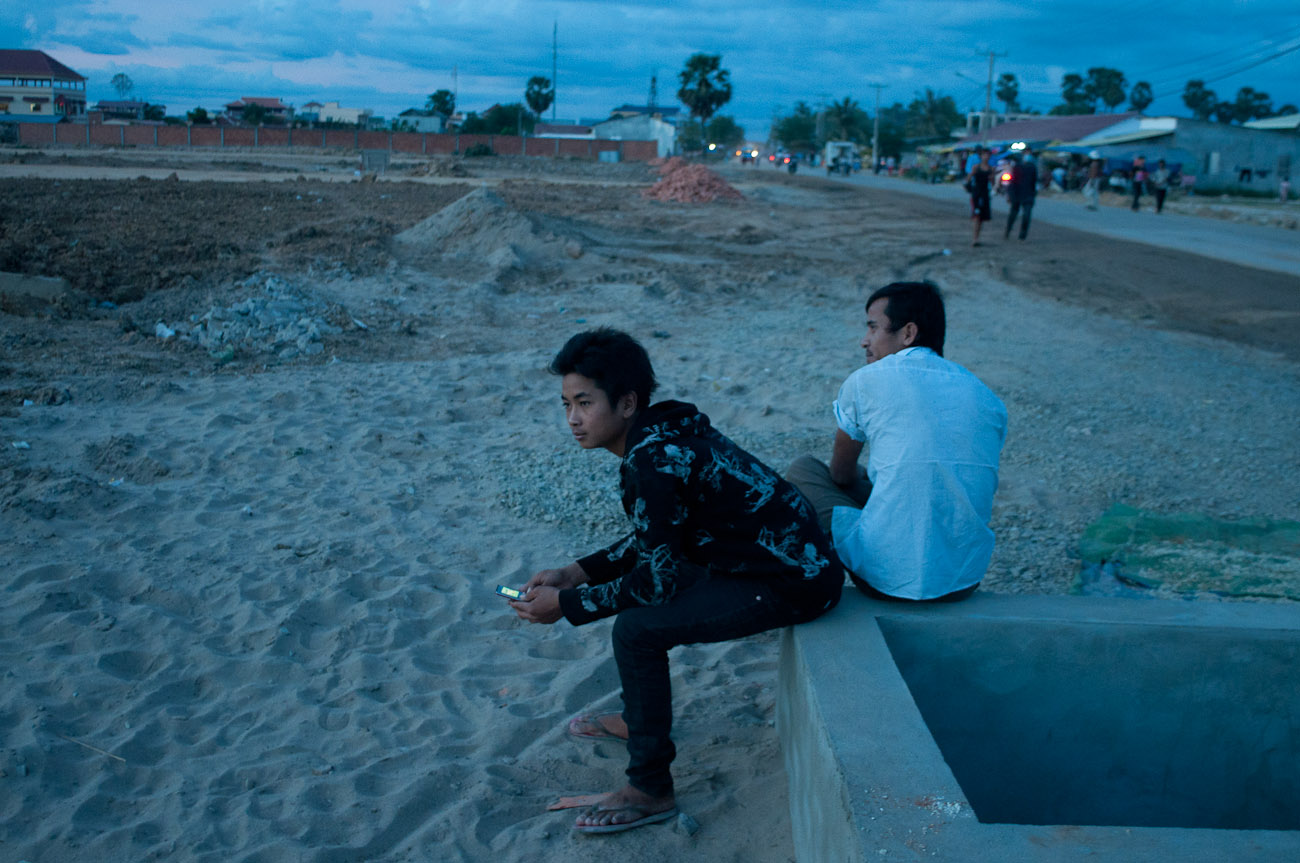 Construction workers are relaxing after a day's work at the New World mega housing project on the outskirts of Phnom Penh. They are mostly from the countryside and earn anywhere between five to ten dollars per day depending on their skills. December 2011