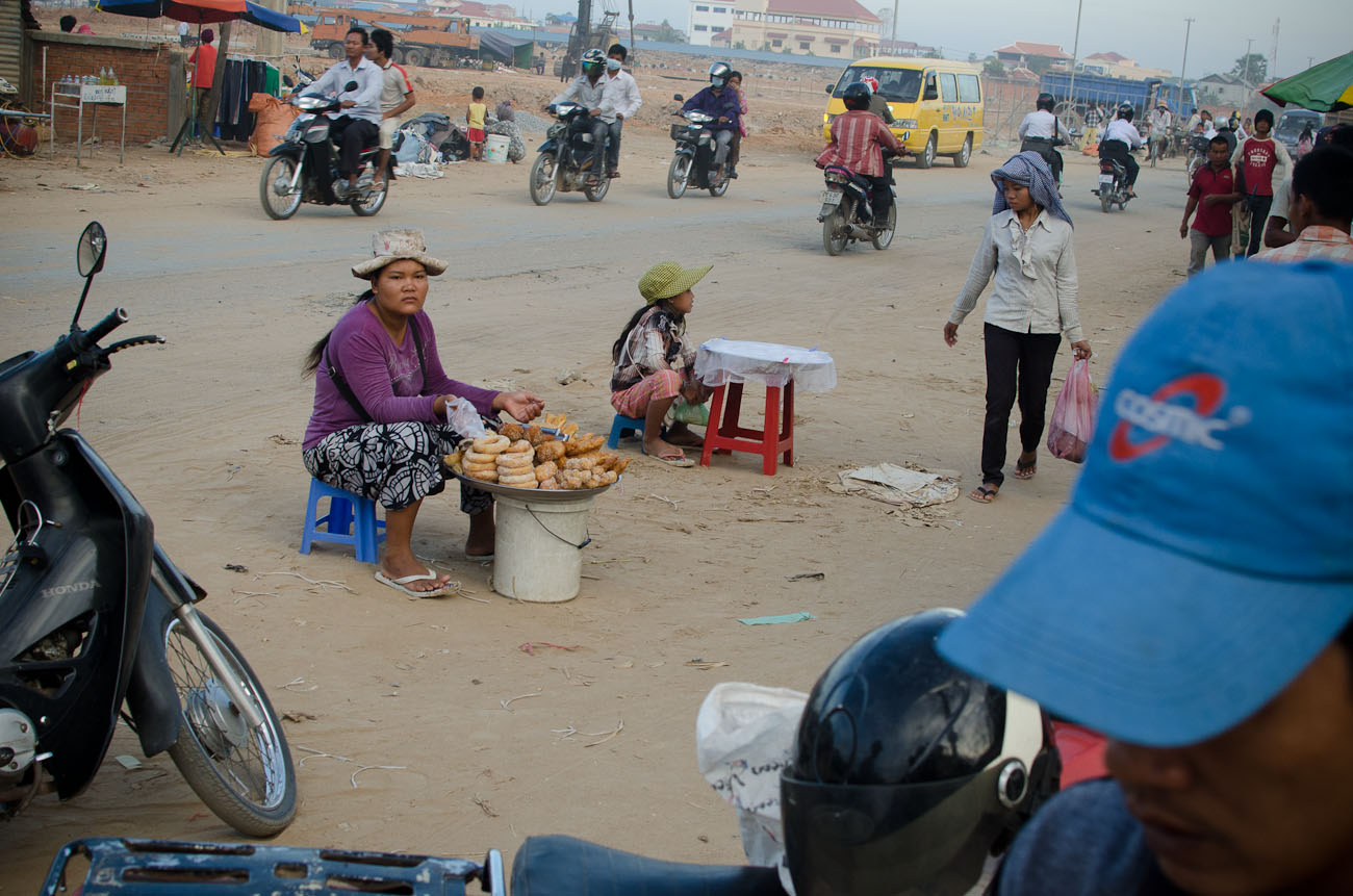 Construction workers shopping for dinner on the way home to their communal dwelling at the New World mega housing project on the outskirts of Phnom Penh. They are mostly from the countryside and earn anywhere between five to ten dollars per day depending on their skills. December 2011