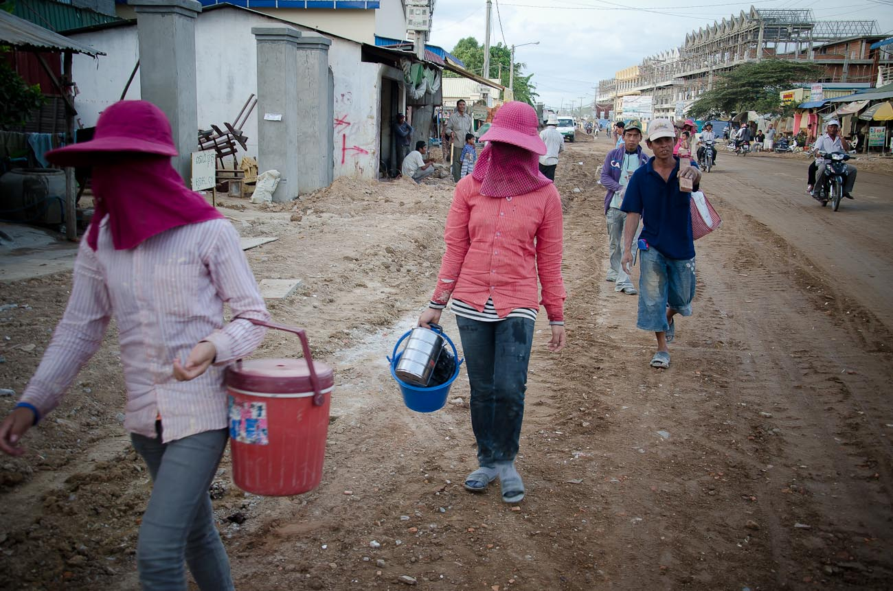 Construction workers returning to their living quarters after a day on the job at the New World mega housing project on the outskirts of Phnom Penh. They are mostly from the countryside and earn anywhere between five to ten dollars per day depending on their skills. December 2011