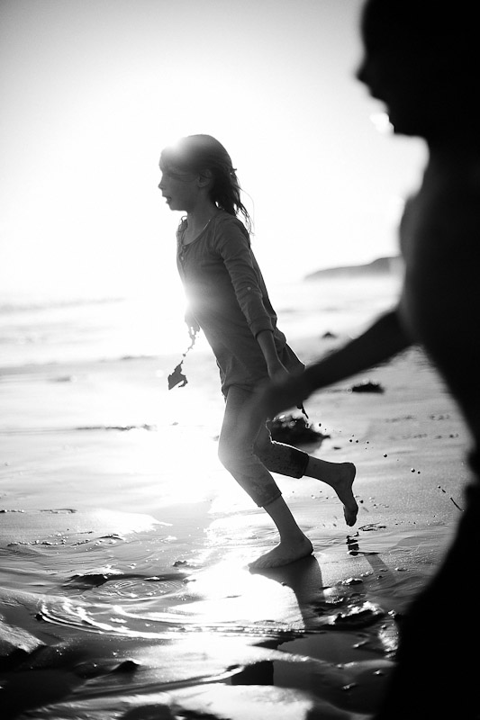 Silhouette of children running on a beach in southern California.