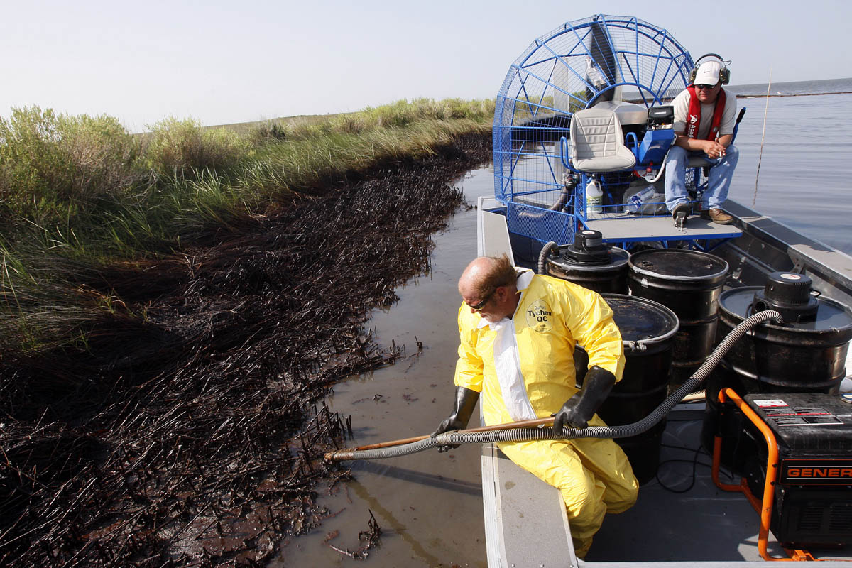 Harold Cline, in yellow, vacuums oil that washed up in a cove in Louisiana's Barataria Bay as air boat pilot John Mouchon looks on.