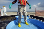 A worker assisting in the cleanup of oil that washed onto a beach in Grand Isle, La., lets water and detergent drip from his gloves while standing in a decontamination pool.