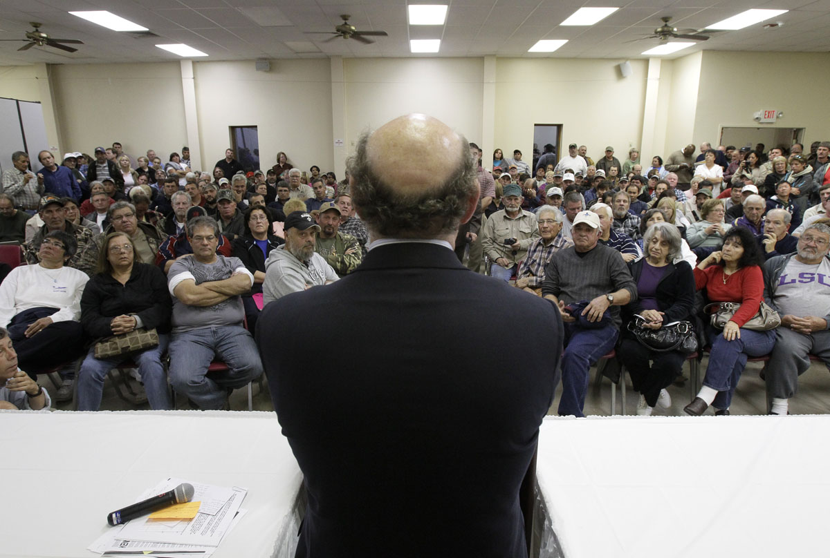 Claimants listen to BP oil spill relief fund administrator Kenneth Feinberg, center, as he speaks at a town hall meeting in Grand Isle, La.