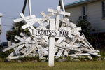 A cross with words referring to promises made by officials responding to the Deepwater Horizon oil spill stands in front of a pile of crosses symbolizing things that were impacted by the spill in Grand Isle, La., one year after the nation's worst offshore oil spill began.