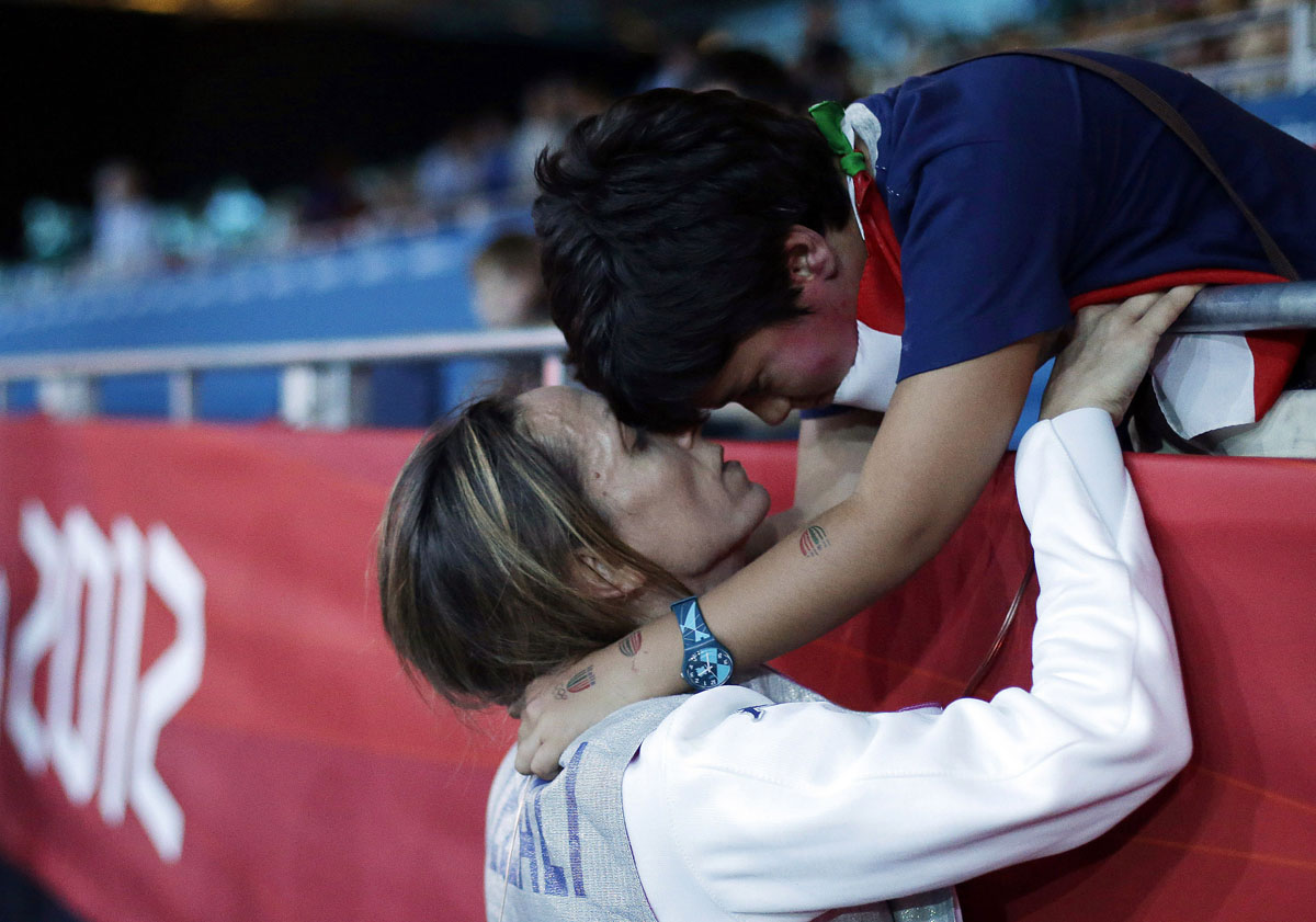 Italy's Valentina Vezzali, left, celebrates with her seven-year-old son Pietro Giuguano after winning a semifinals match against France at women's team foil fencing at the 2012 Summer Olympics in London.