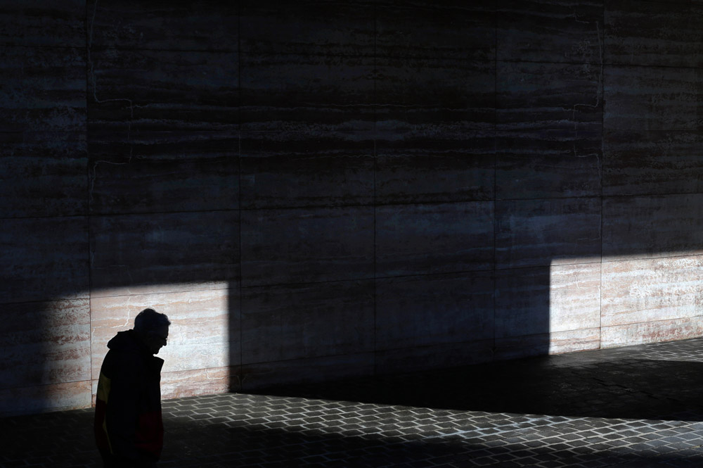 A man walks past a patch of sunlight outside of an office building in Baltimore.