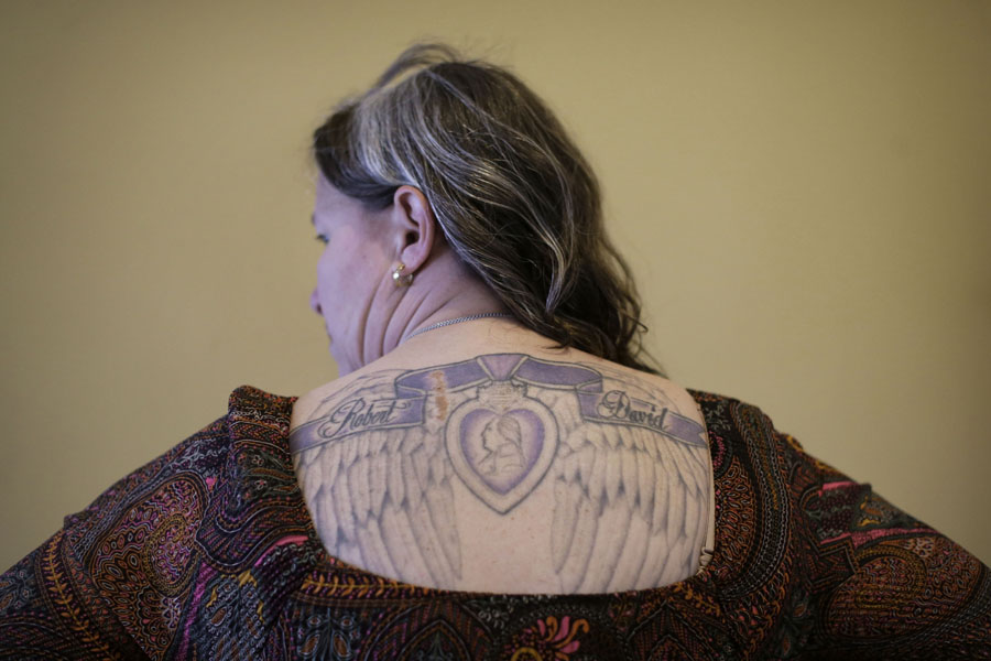 U.S. Marine Corps veteran Rosie Noell displays a tattoo depicting her sons' names and a Purple Heart that she was awarded in her home in Sneads Ferry, N.C.