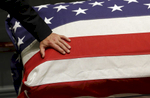 Vice President Joe Biden rests his hand on a flag-draped casket containing the remains of his son, former Delaware Attorney General Beau Biden, during a visitation in Dover, Del. Beau Biden died of brain cancer at age 46.
