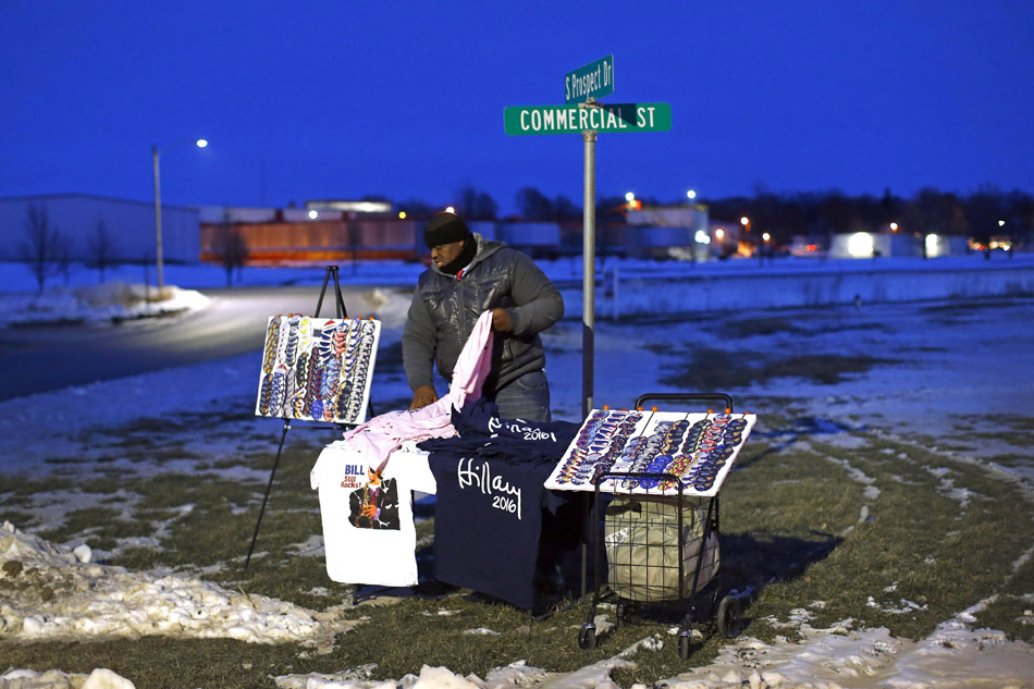 Vincent Reul sets up campaign merchandise on a street corner before a campaign event featuring Democratic presidential candidate Hillary Clinton at the Toledo Civic Center in Toledo, Iowa.