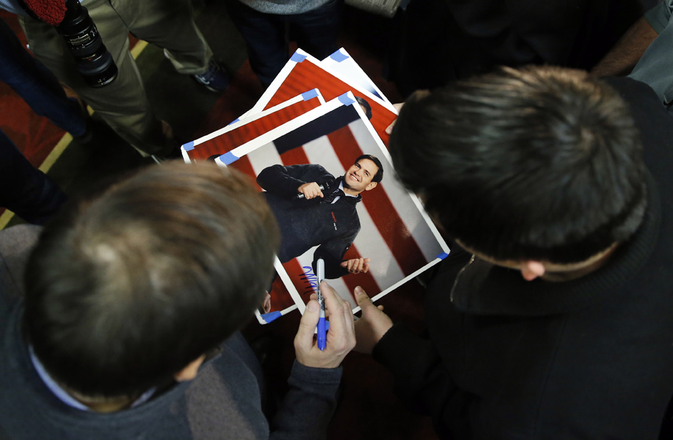 Republican presidential candidate, Sen. Marco Rubio, R-Fla., left, autographs photos after speaking at a town hall in West Des Moines, Iowa.