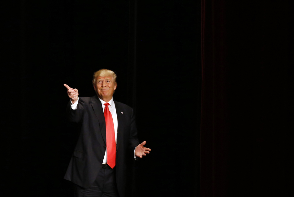Republican presidential candidate Donald Trump gestures as he walks onstage for a campaign event at the Orpheum Theatre in Sioux City, Iowa.